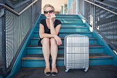 Female Lost in Thought Traveling Alone with Suitcase
