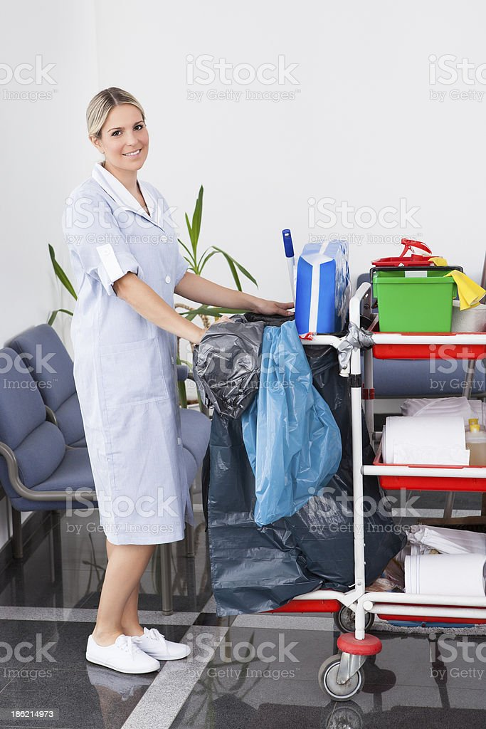 Female made pushing the cleaning trolley stock photo