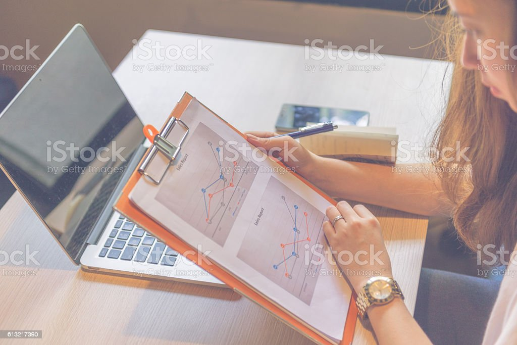 Female manager reading report and working with laptop stock photo