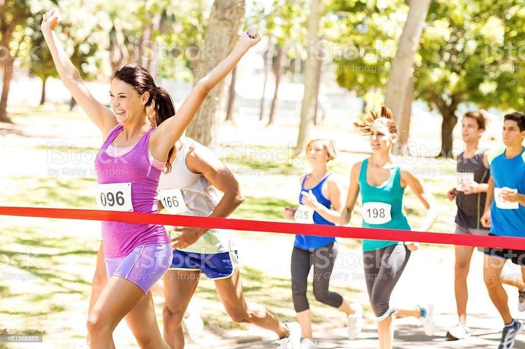 Female Marathon Runner Crossing Finish Line stock photo