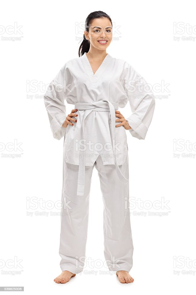 Full length portrait of a young female martial artist in a white...