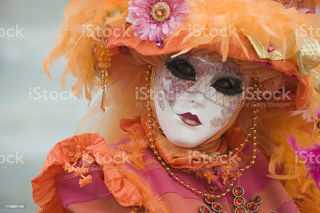 Female mask with beautiful orange costume at carnival in Venice royalty-free stock photo