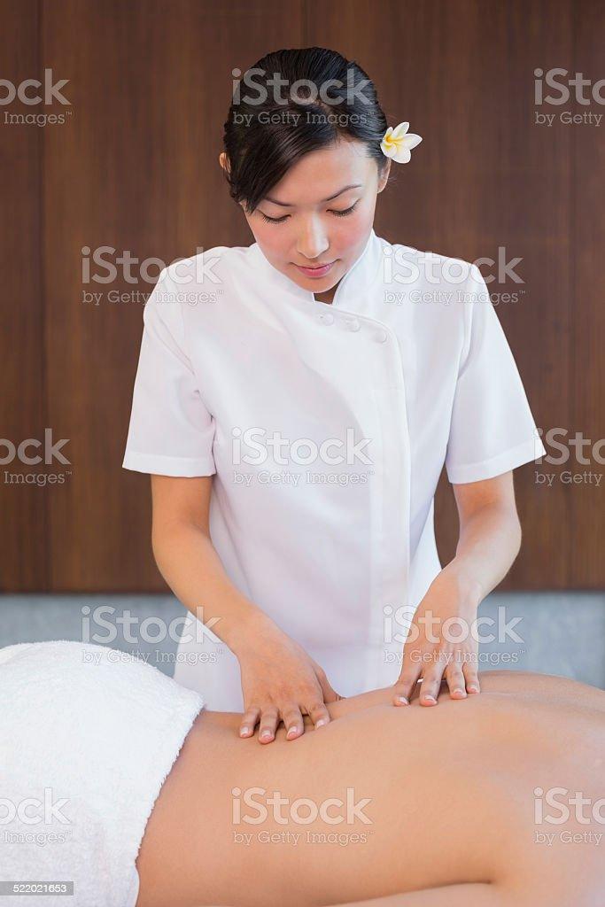Female masseur massaging mans back at spa center stock photo