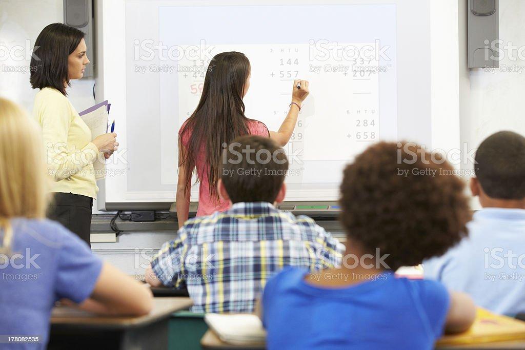Female math students writing answers on a whiteboard stock photo