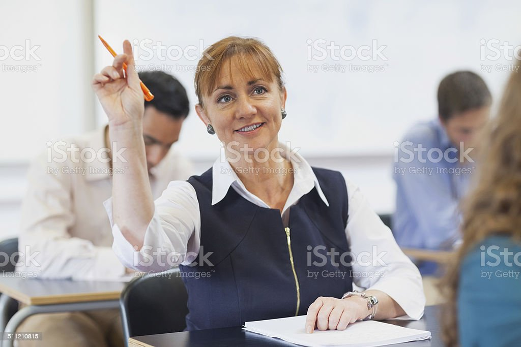 Female mature student raising her hand stock photo