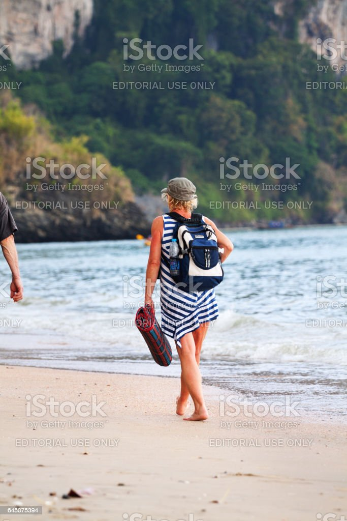 Female mature tourist with backpack on beach stock photo