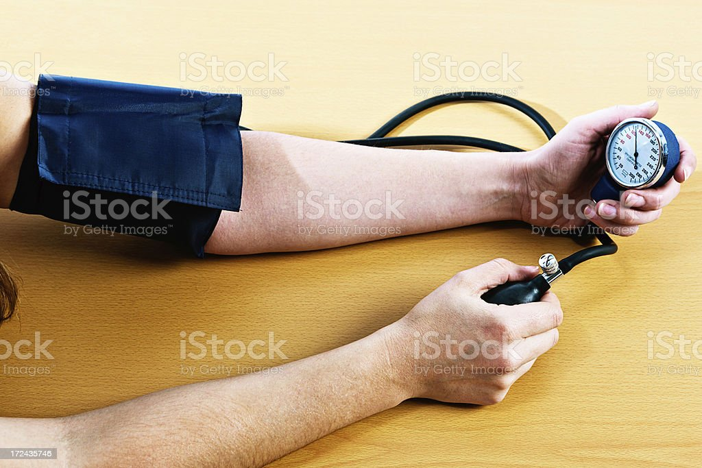 Female measures her own blood pressure royalty-free stock photo