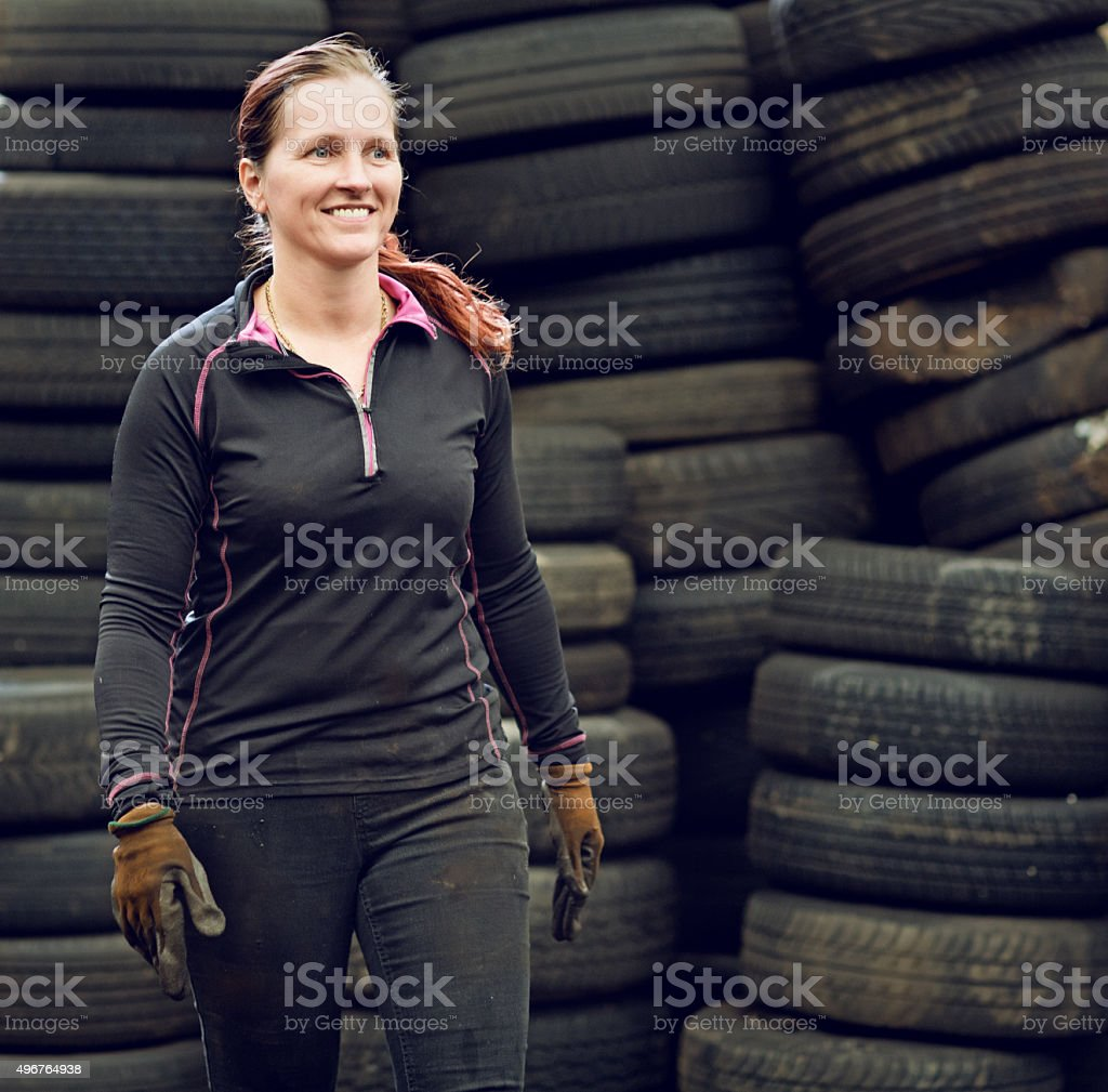 female mechanic carrying tires stock photo