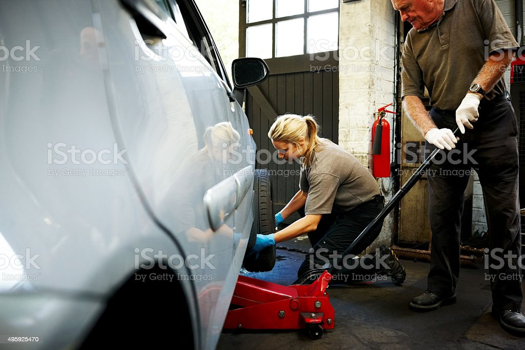 Female mechanic changing tires in garage stock photo