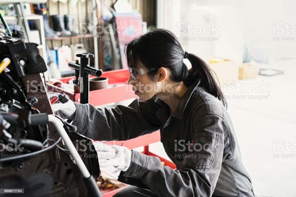 Female mechanic inspecting a damaged car in an auto repair garage stock photo