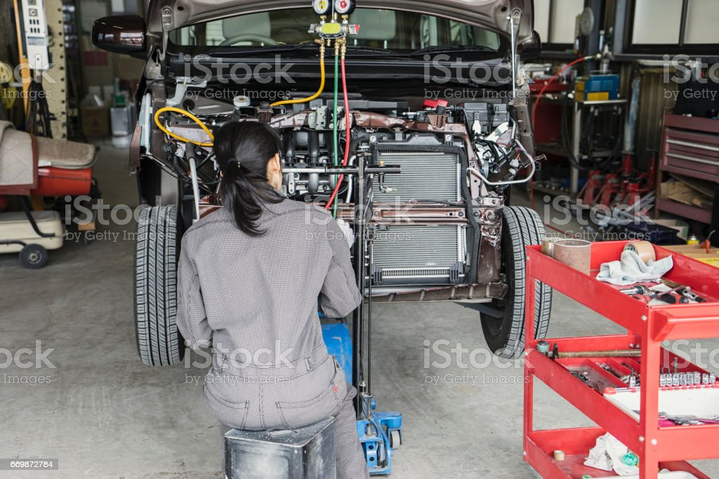 Female mechanic inspecting a damaged car with digital tablet in an auto repair garage stock photo
