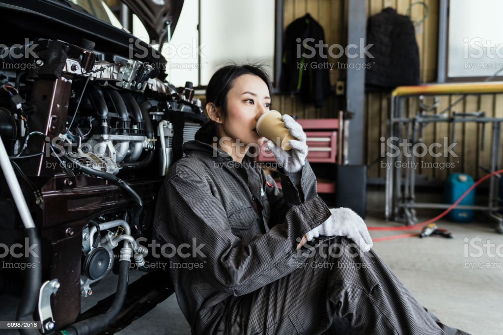 Female mechanic resting in an automotive repair shop stock photo