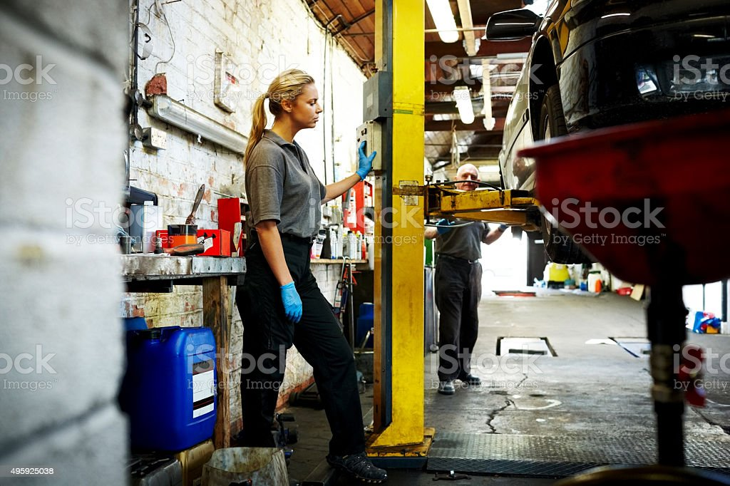 Female mechanic working in automobile garage stock photo