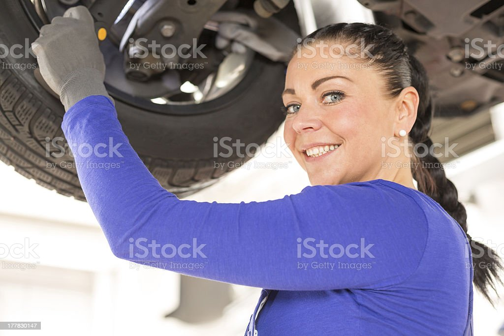 Female mechanic working on car at hydraulic ramp royalty-free stock photo