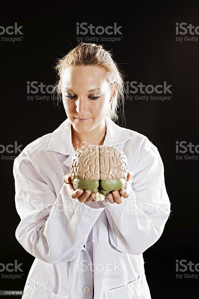 Female medical professional holds model brain, smiling gently stock photo
