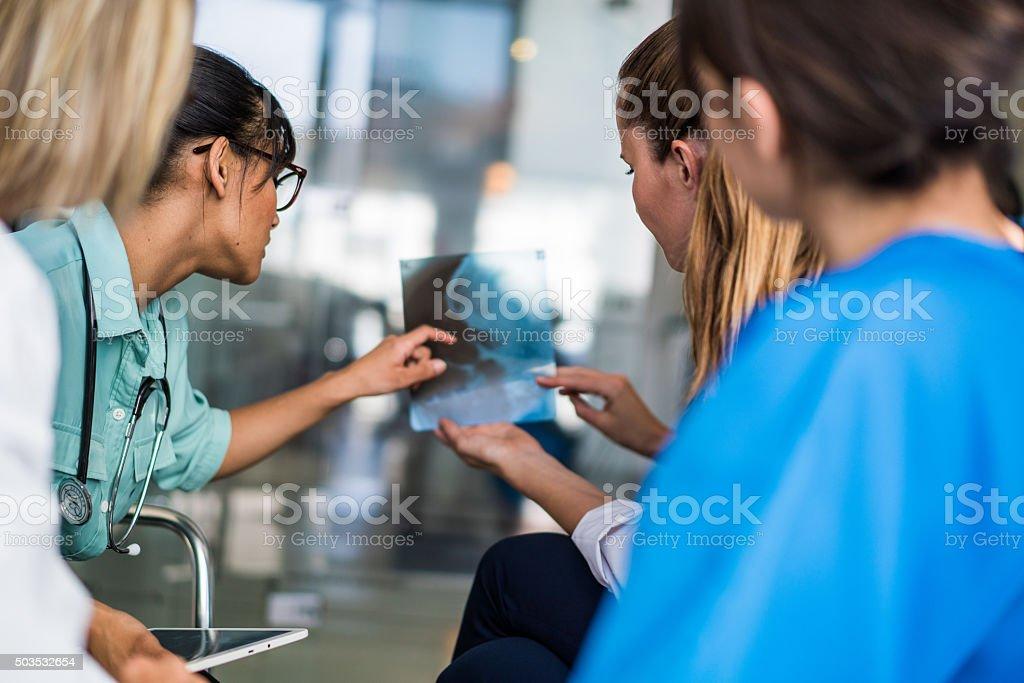 Female medical team examining x-ray stock photo