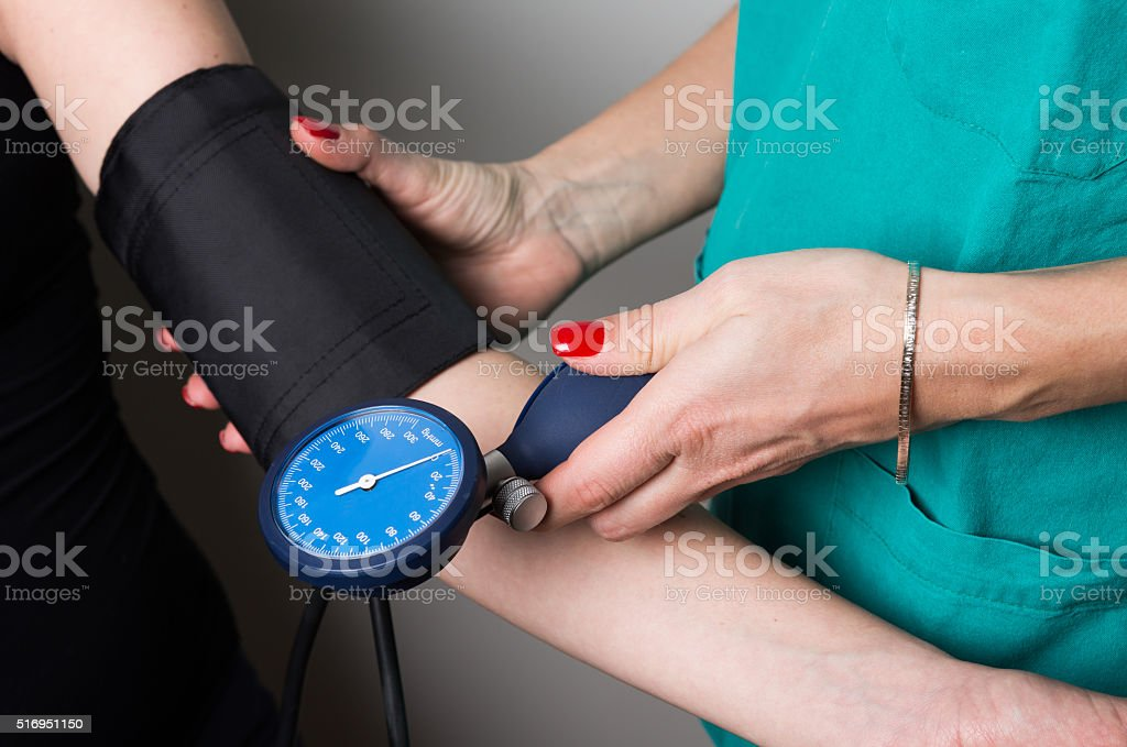 Female medicine doctor measuring blood pressure stock photo