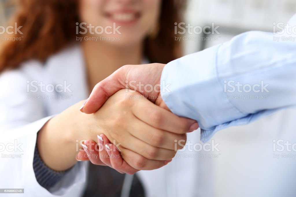 Female medicine doctor shake hand as hello with businesswoman stock photo