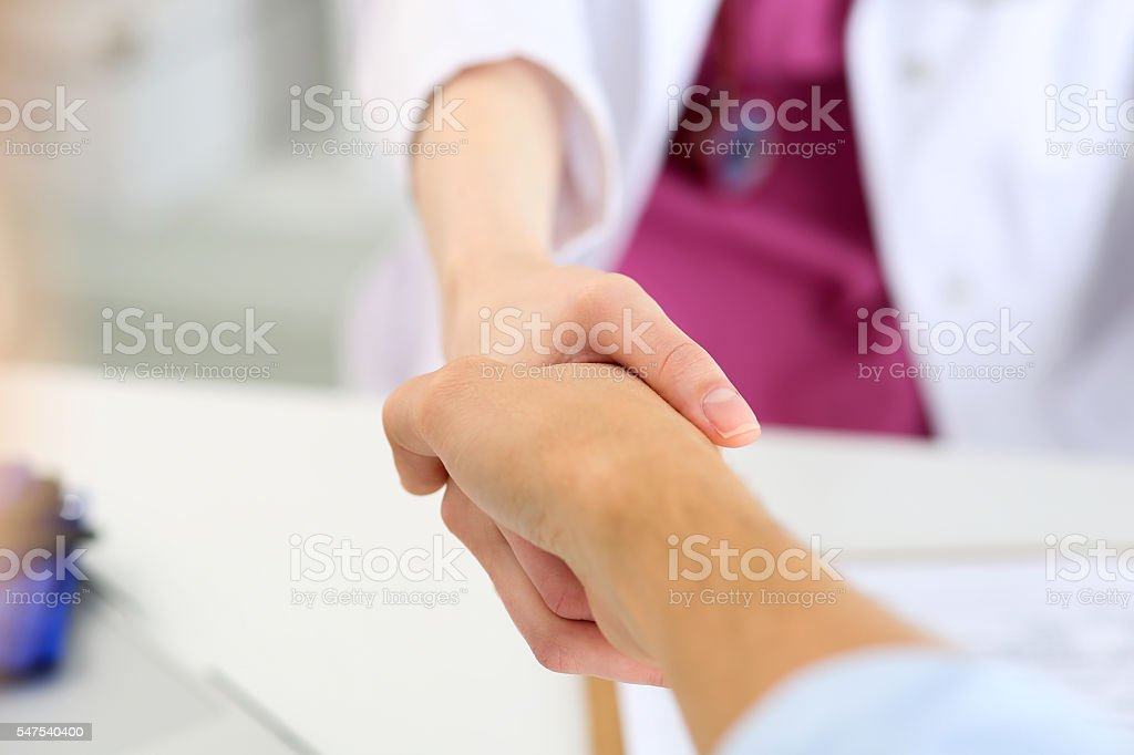 Female medicine doctor shake hand as hello with male patient stock photo