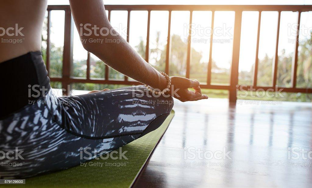 Female meditating in lotus pose at yoga class stock photo