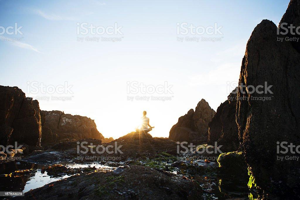 Female meditating on the rocks royalty-free stock photo