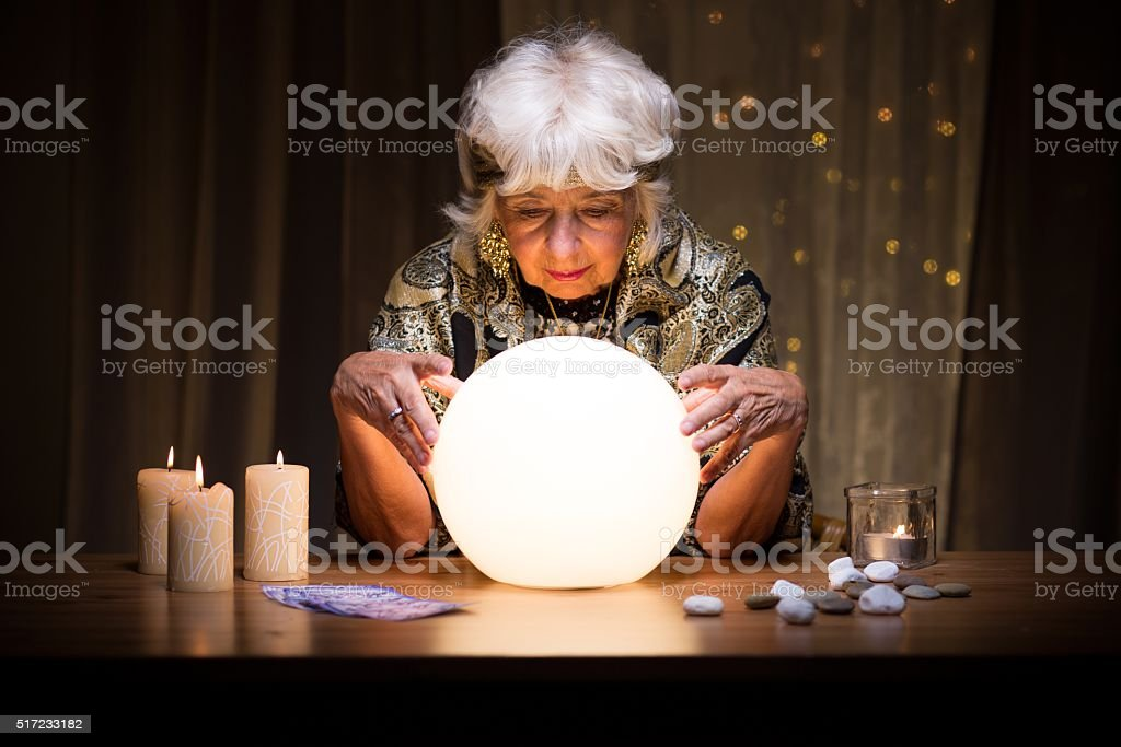 Female medium with crystal ball stock photo