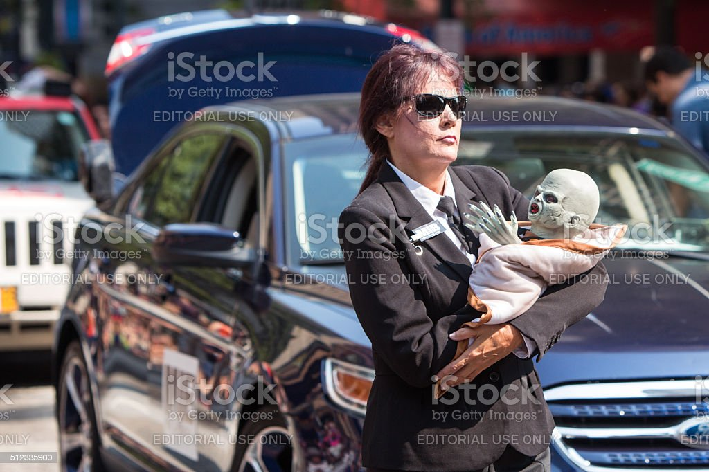 Female Men In Black Agent Carries Alien Baby At Parade stock photo