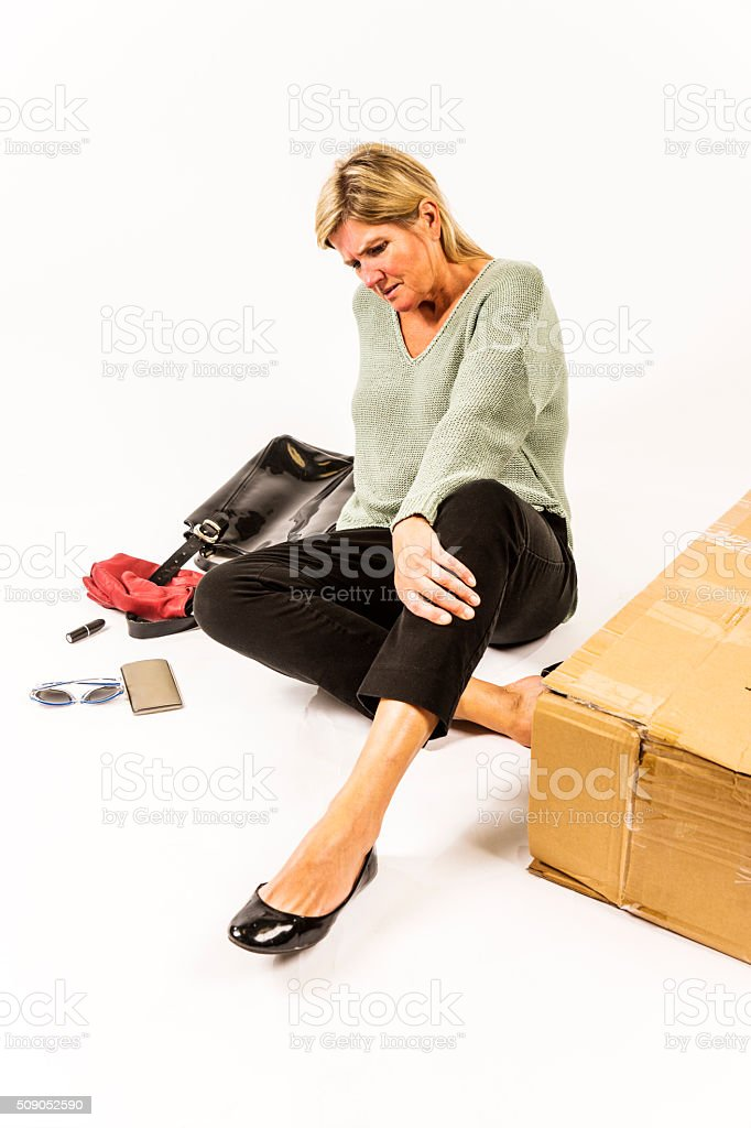 Female, middle-aged shopper tripped over a box stock photo