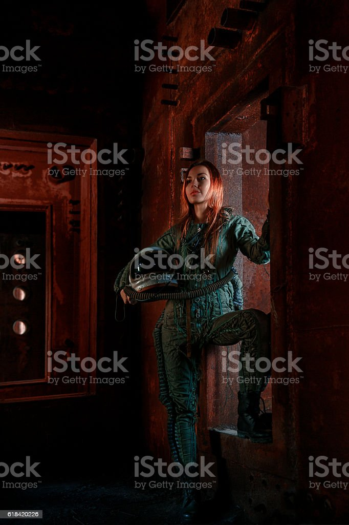 Female military pilot in bunker with helmet and flight costume stock photo