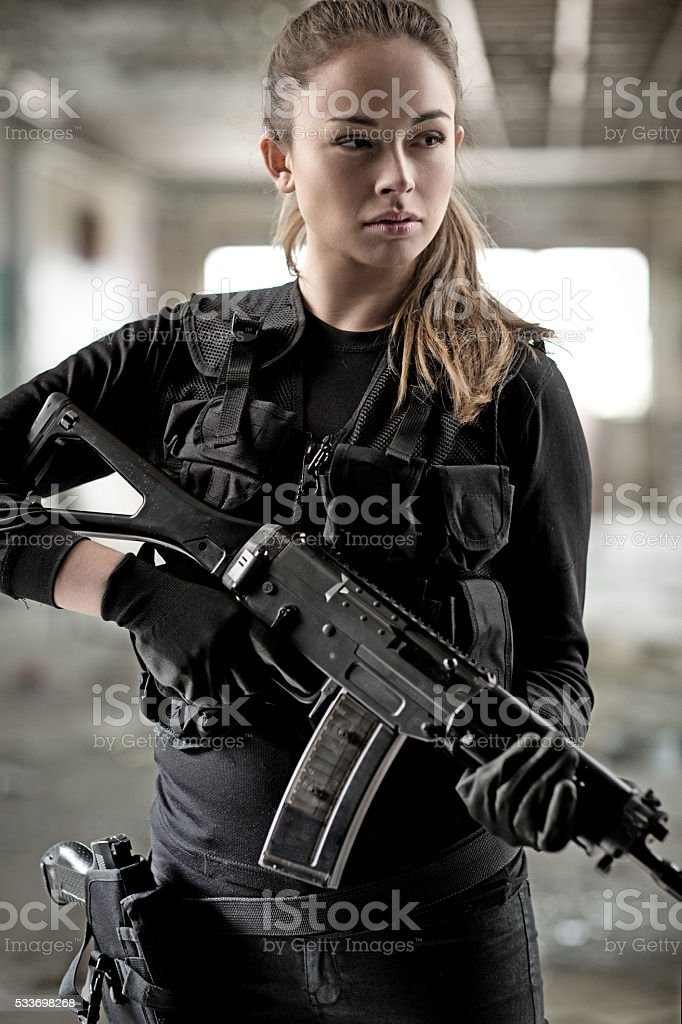 Female military swat team member holding rifle in abandoned warehouse stock photo
