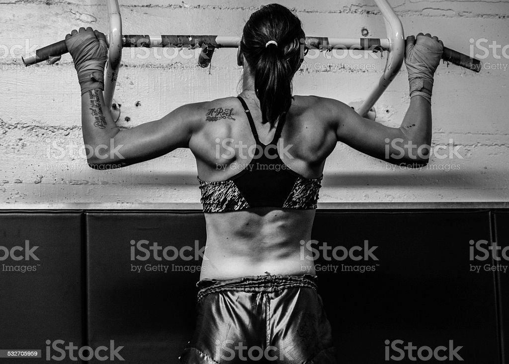 Female MMA Fighter doing pull-ups stock photo
