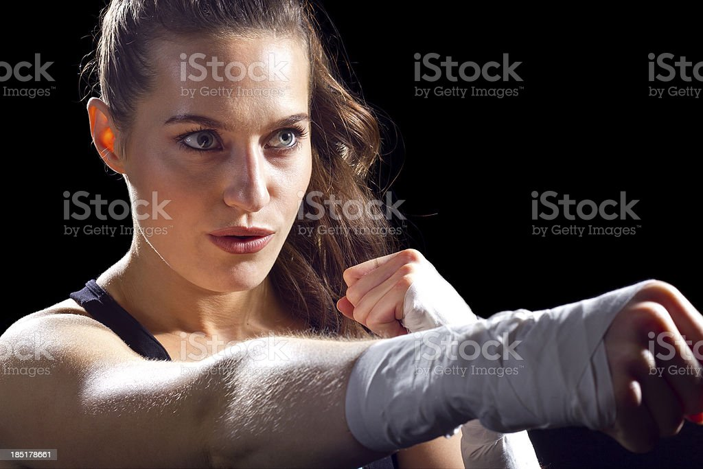 Female MMA Fighter Holding Fist Out Punching on Black Background royalty-free stock photo