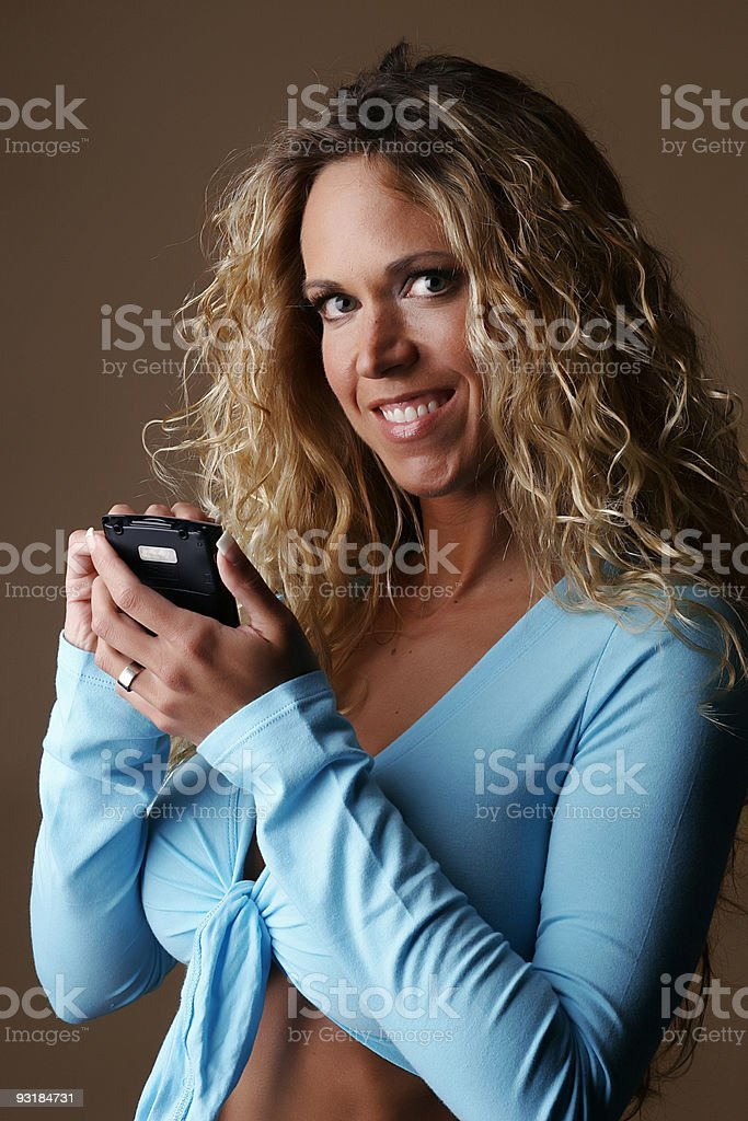 Female model smiling while using a PDA royalty-free stock photo