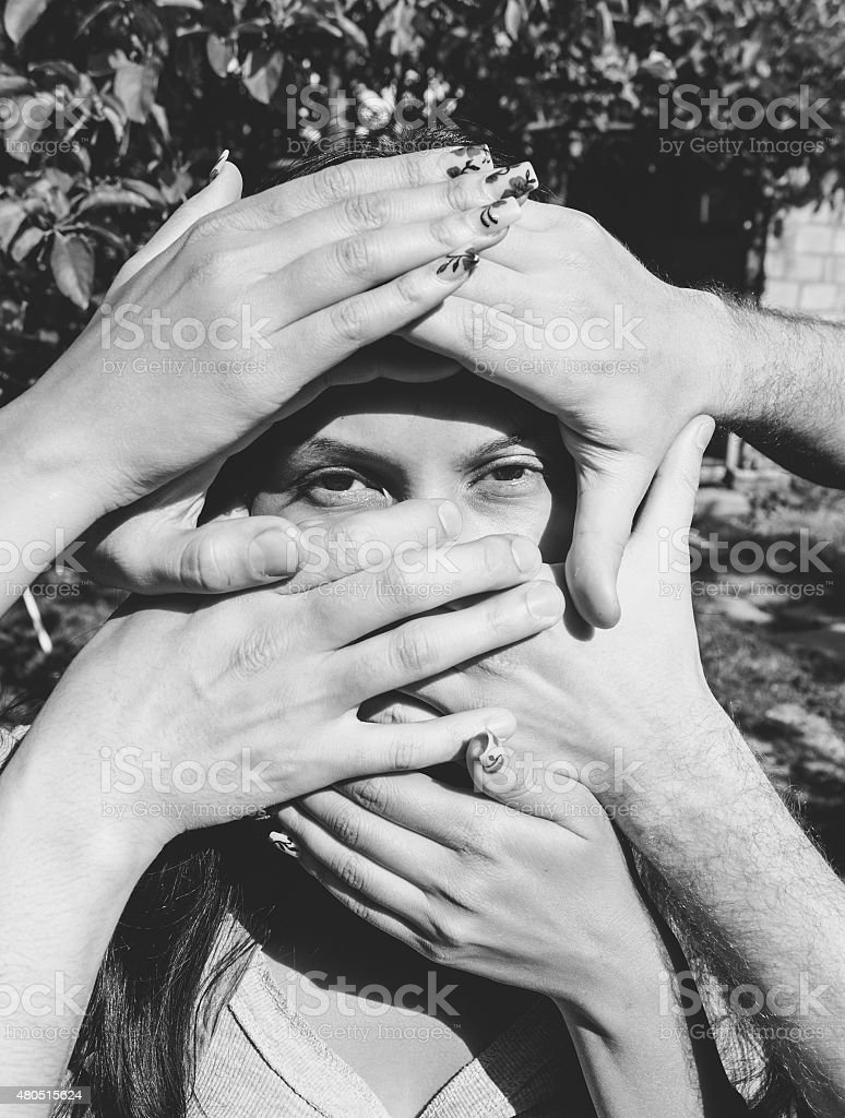 Female Model with several Hands on Her Face stock photo