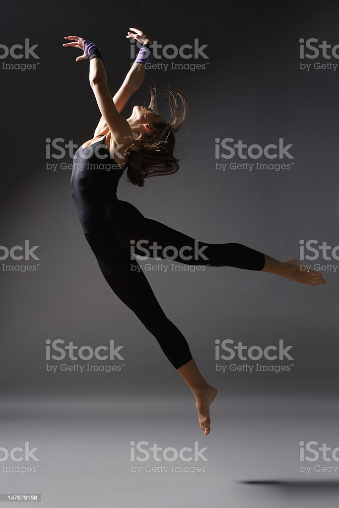 Female modern ballet dancer jumping with arms raised royalty-free stock photo