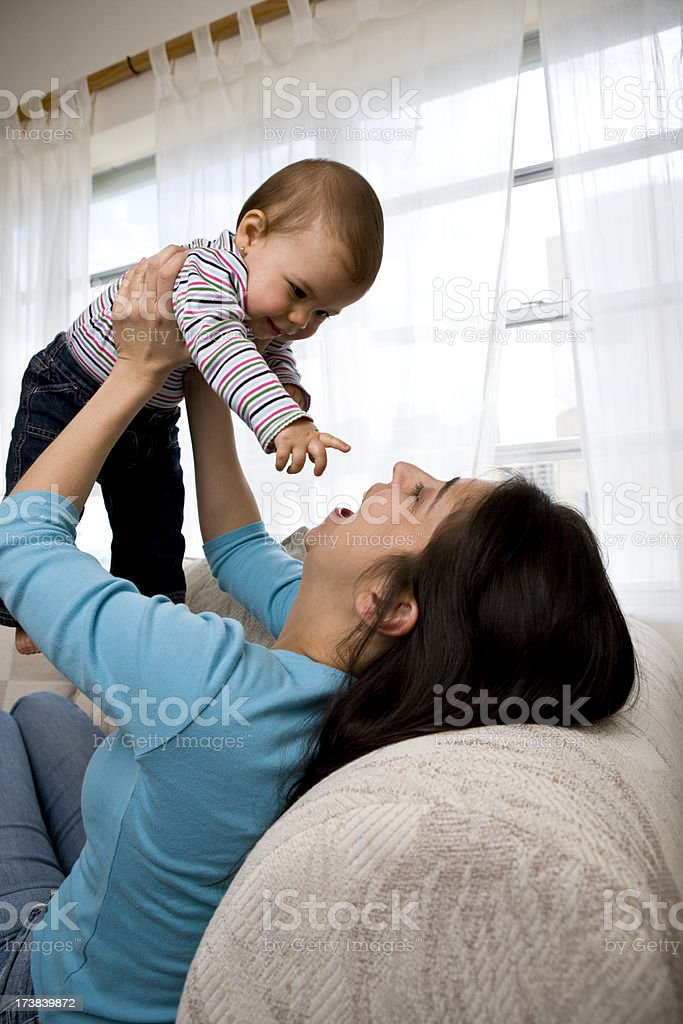 Female mother playing with infant daughter in air royalty-free stock photo