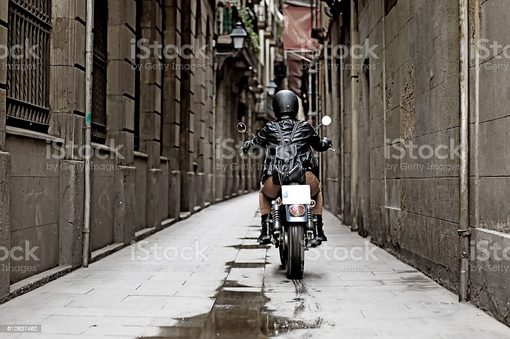 Female motorcyclist riding a vintage motorbike in european city centre stock photo