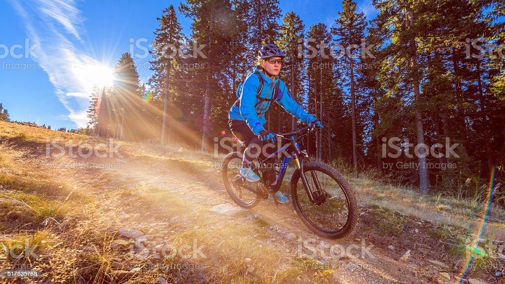 Female mountain biker riding down hill stock photo