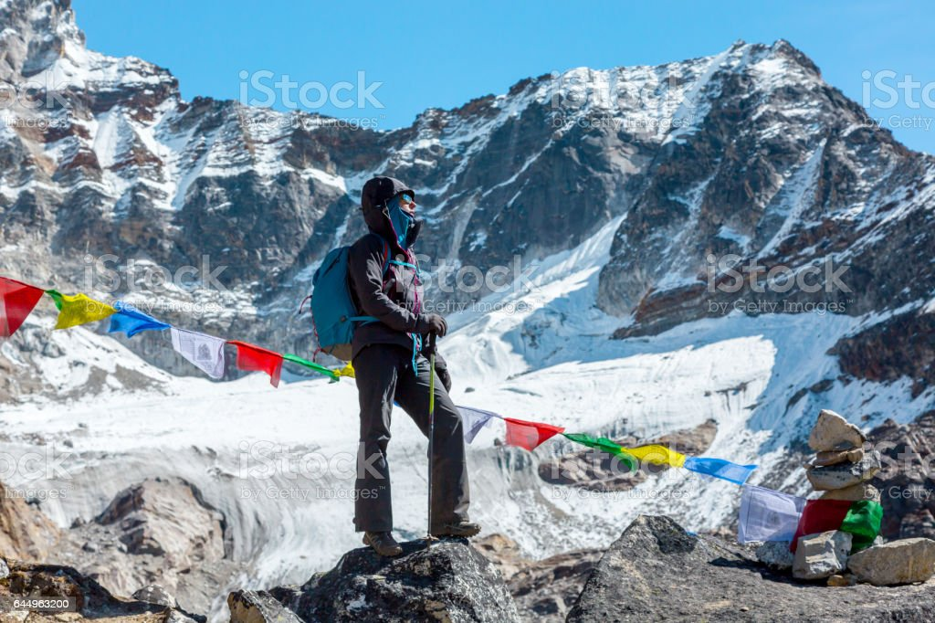 Female Mountain Climber staying on Stone Top in high Mountains stock photo