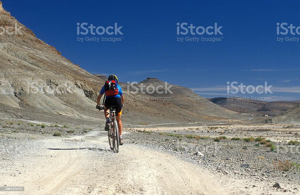 Female Mountainbiker in the mountain desert of Morocco stock photo