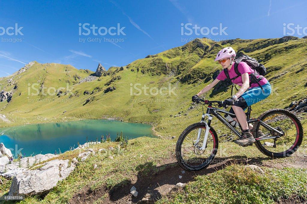 Female mountainbiker is approaching Urdensee, Switzerland stock photo