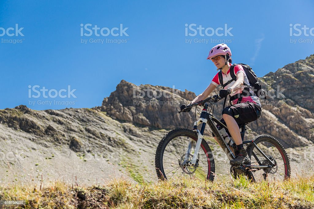 Female mountainbiker uphill in Swiss Mountains stock photo