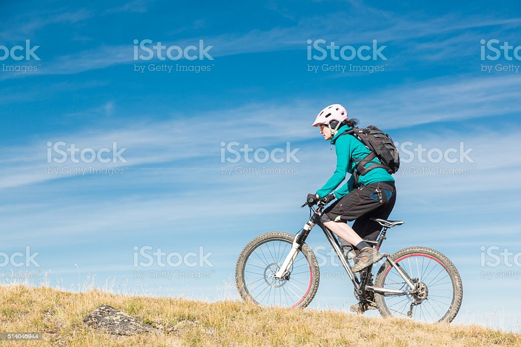 Female mountainbiker uphill, Switzerland stock photo