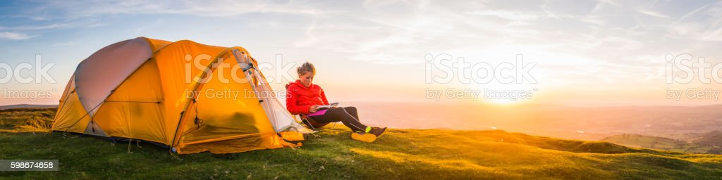 Female mountaineer relaxing beside tent idyllic summer sunset peak panorama stock photo