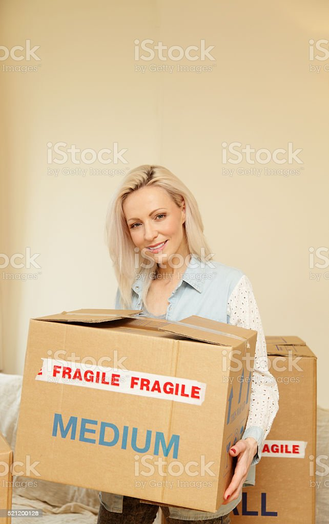 female moving house-carrying boxes stock photo