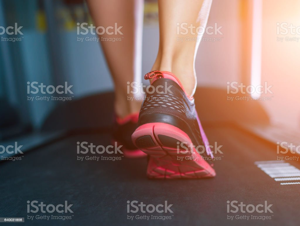 Female muscular feet in sneakers running on the treadmill. stock photo