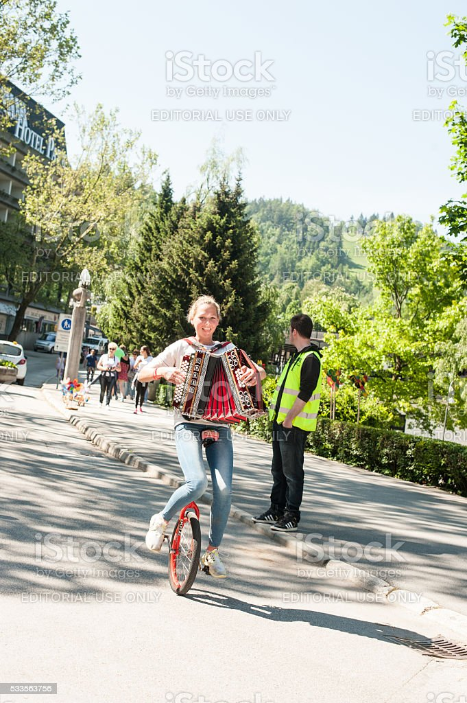 Female musician riding unicycle stock photo