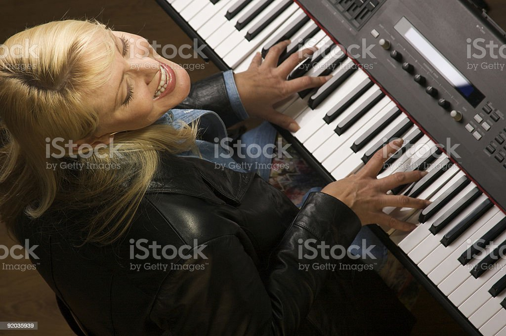 Female Musician Sings and Plays the Piano stock photo