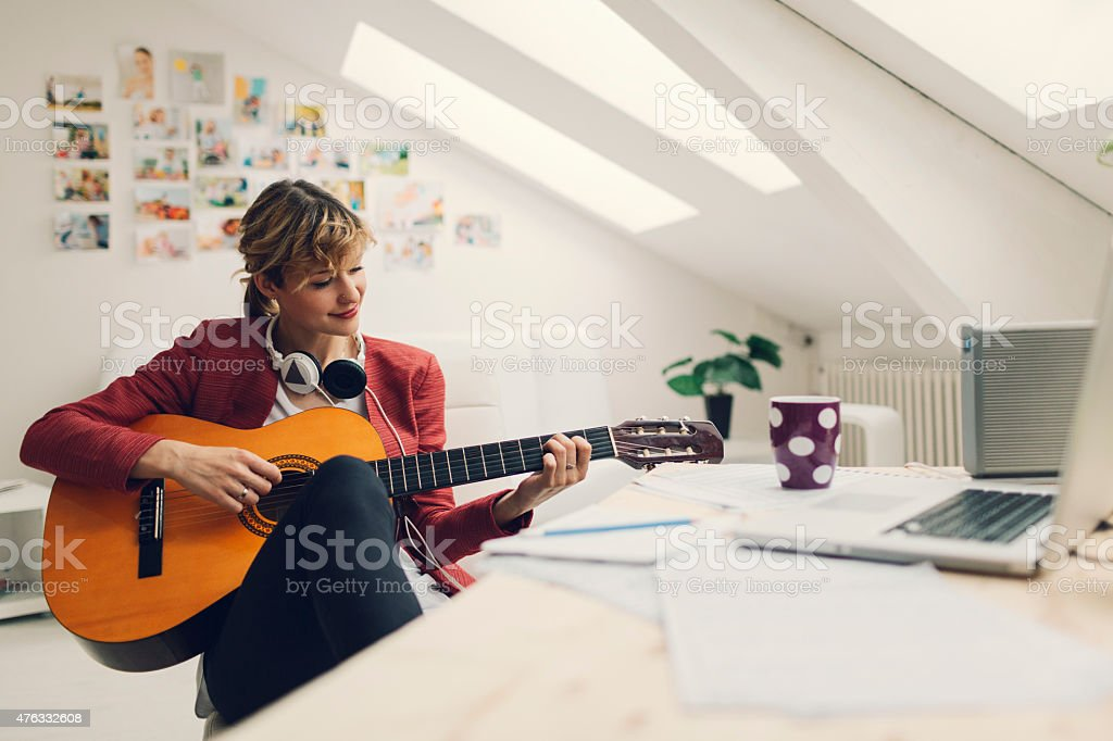 Female Musician Working In Her Home Recording Studio. stock photo