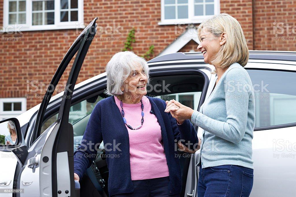 Female Neighbor Giving Senior Woman A Lift In Car stock photo
